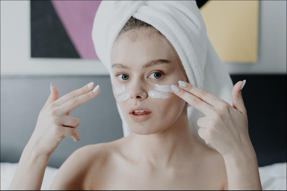 Woman Applying Cream on Her Cheeks